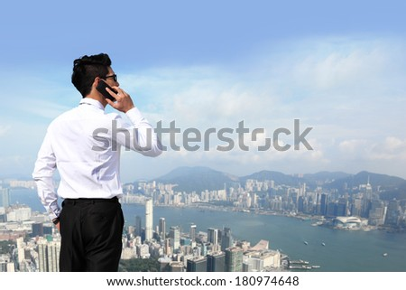 Happy business men call by smart phone on business architecture background, asia, hong kong - stock photo