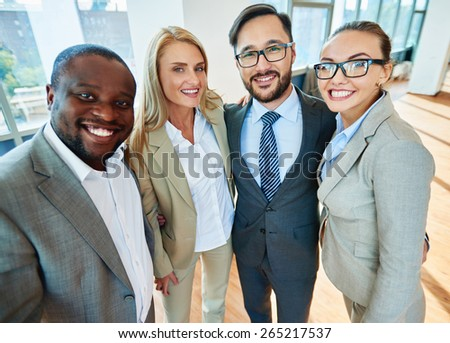 Happy business partners in formalwear looking at camera in office