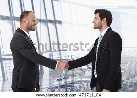 Happy business partners shaking hand before meeting at office board room.