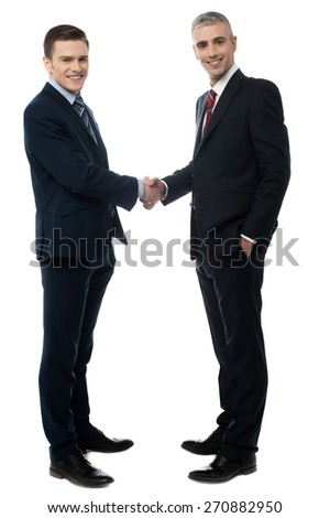 Happy business partners shaking hands - stock photo