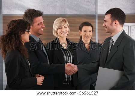 Happy business partners shaking hands in meeting room, smiling. - stock photo