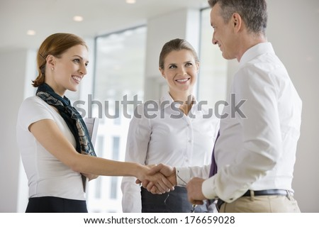 Happy business partners shaking hands in office - stock photo
