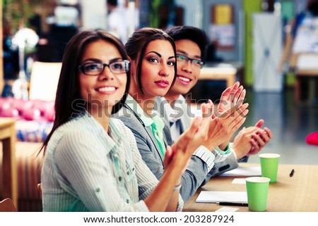 Happy business people applauding in a meeting. Business concept. - stock photo