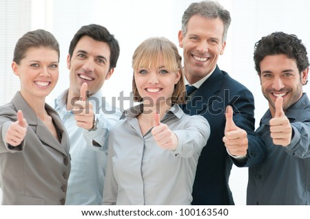 Happy business people cheering and showing thumb up at office - stock photo