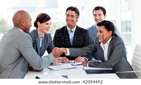 Happy business people closing a deal in a meeting - stock photo