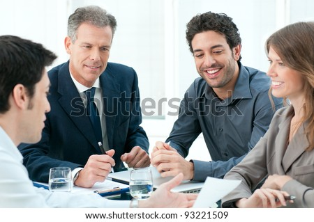 Happy business people discussing together their strategy at meeting in office - stock photo
