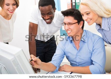 Happy business people gathered around laptop looking at monitor in the office - stock photo