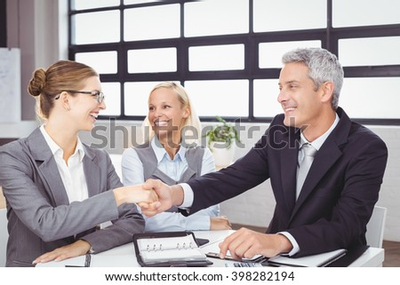 Happy business people handshaking during meeting at desk in office - stock photo