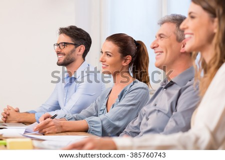 Happy business people in a row listening a seminar in office boardroom. A team of businesspeople sitting as panel for conducting job interview. Happy young team of business people a presentation.