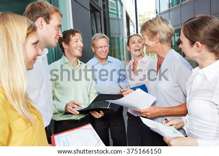 Happy business people laughing and talking outside the office