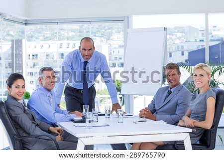Happy business people looking at camera in the office - stock photo