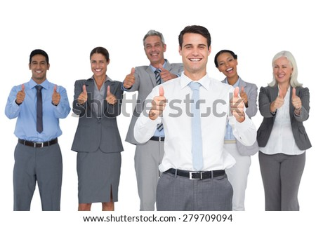 Happy business people looking at camera with thumbs up in office - stock photo