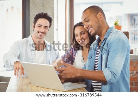 Happy business people pointing towards laptop in creative office - stock photo