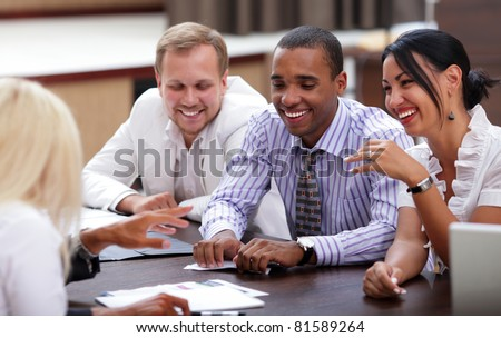 Happy business people sitting around the table at the meeting - stock photo
