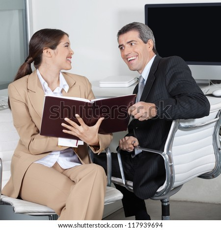 Happy business people smiling with order book in the office - stock photo