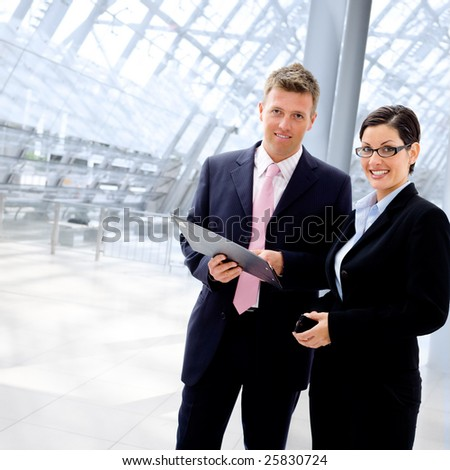 Happy business people talking at office lobby, smiling. - stock photo