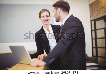Happy business people talking while standing by counter at office