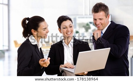 Happy business people with laptop working together laughing. - stock photo