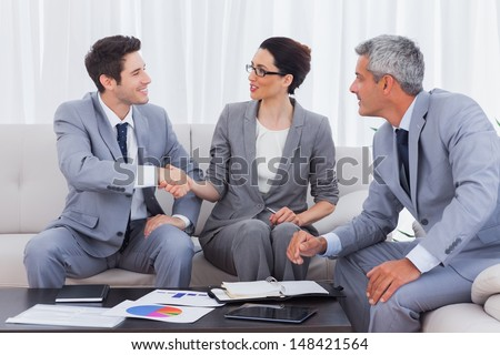 Happy business people working and talking together on sofa at office - stock photo