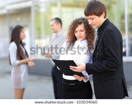 Happy business people working on the background of a modern office building - stock photo