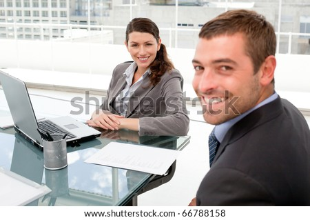 Happy business people working together on a laptop during a meeting - stock photo
