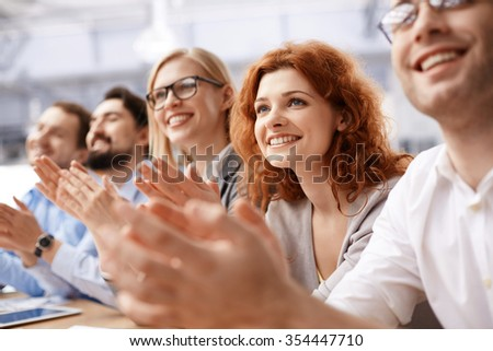Happy business team applauding at conference - stock photo
