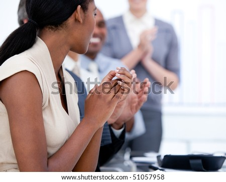 Happy business team applauding in a meeting in a company