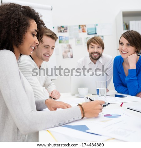 Happy business team composed of a diverse multiethnic group of young people sitting in a meeting attentively watching one woman as she reads from a document - stock photo