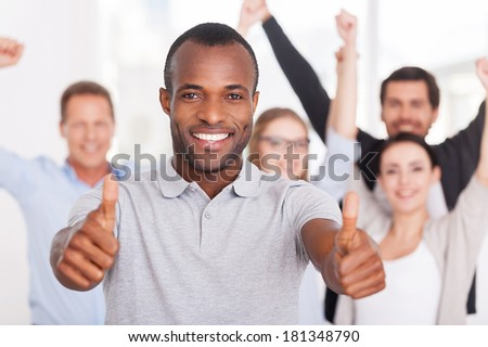 Happy business team. Happy young African man showing his thumbs up you and smiling while group of people in casual wear standing on background - stock photo