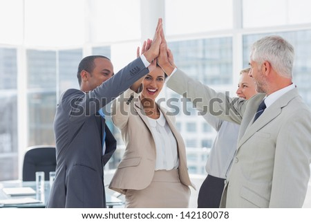 Happy business team high fiving in the office - stock photo