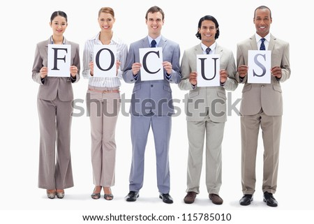 Happy business team holding the letters of FOCUS against white background - stock photo