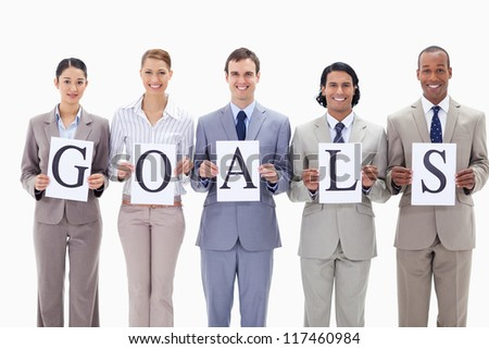 Happy business team holding the letters of GOALS against white background - stock photo