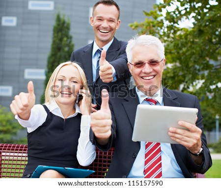 Happy business team holding their thumbs up with tablet computer in a park - stock photo