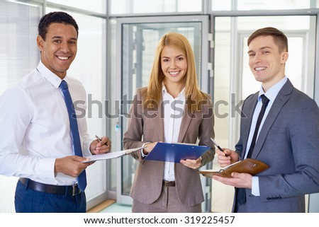 Happy business team in formalwear looking at camera in office