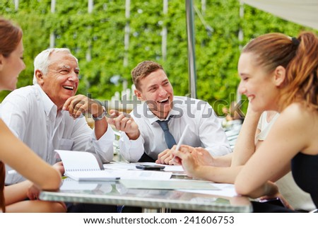 Happy business team laughing during planning in a meeting outdoors