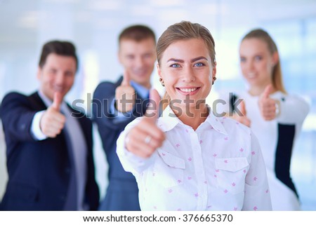 Happy business team showing thumbs up in office - stock photo