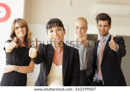 Happy business team showing thumbs up in the office