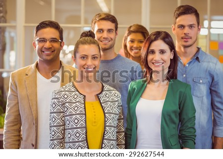 Happy business team smiling at camera in the office - stock photo