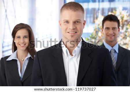 Happy business team standing in office, focus on smiling young businessman looking at camera.