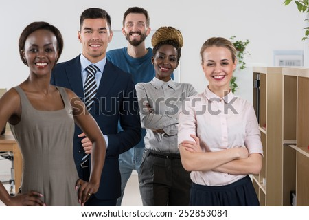 Happy business team standing together at office - stock photo