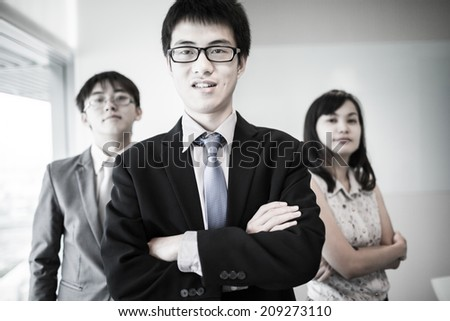 Happy business team with arms crossed at the office.Asian - stock photo