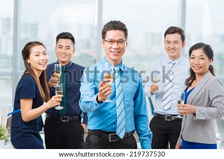 Happy business team with champagne glasses - stock photo