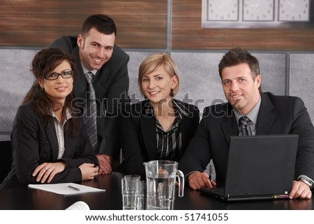 Happy business team working in meeting room, looking up to camera, smiling. - stock photo