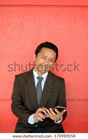 Happy business with mobile phone pose with red background - stock photo