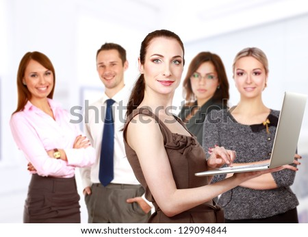 Happy business woman holding a modern laptop computer with team - stock photo