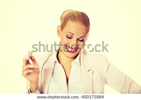 Happy business woman holding broken cigarette - stock photo