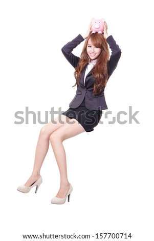 Happy business woman holding pink piggy bank and sitting on something isolated against white background, asian male model - stock photo
