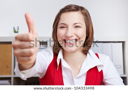 Happy business woman in her office holding thumbs up - stock photo