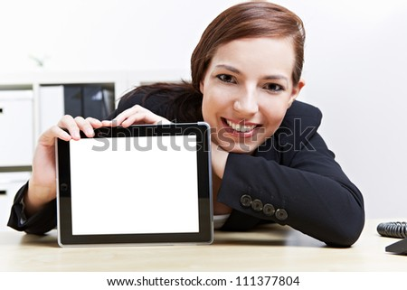 Happy business woman in her office presenting a tablet computer - stock photo