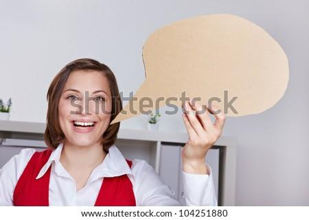 Happy business woman in offce holding empty cardboard speech balloon - stock photo